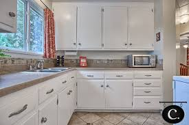 brushed nickel kitchen cabinet knobs the kitchen has been completely renovated with fresh white cabinets brushed nickel hardware ceramic tile floor and a modern tile backsplash detail