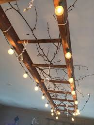 a vintage wooden ladder makes great lighting this one is wrapped with globe lights