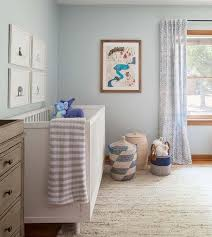 charming blue and white nursery features a white crib placed on a white and gold jute rug against a light blue wall beneath the animal print prints