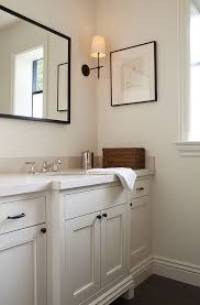 black and white bathroom furniture. Cream Powder Room Features A Vanity Adorned With Bronze Knobs Placed Under Black Mirror Illuminated By Thomas O\u0027Brien Bryant Sconces And White Bathroom Furniture
