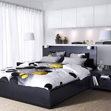 A bedroom with a black-brown MALM bed, BEST storage with white doors and