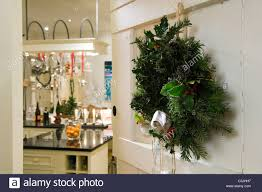 wreath on white open door with view through to kitchen with festive decorations