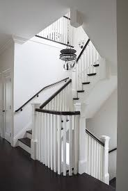 Elegant white staircase with glossy brown hand rail illuminates by The  Urban Electric Co. Dover Bell light.