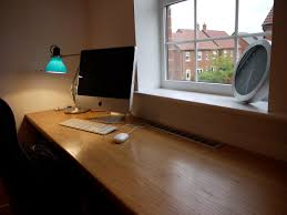 long wooden computer desk behind the window in small home office