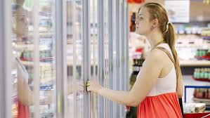 group of people walking through the glass sliding doors young woman ing dairy or refrigerated groceries at the supermarket in the refrigerated section