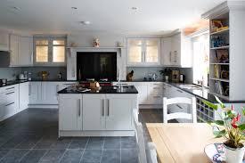 white kitchen cabinets black countertops and dark stone floor tiles