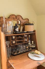 the at home bar from an antique drop front secretary desk styled with vintage barware