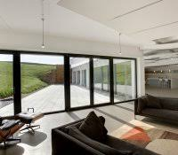 empty living room in farm house high ceiling with beam and floor to window  view of