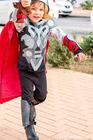 boy dressed in thor costume with hammer raised as if ready to strike