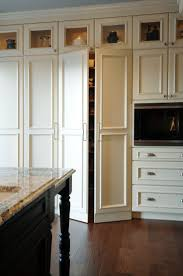 Kitchen with floor to ceiling cabinets and walk-in pantry hidden behind  white cabinet doors.