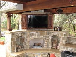 antique double sliding door outdoor tv cabinet over rustic stacked stone fireplace and wooden ceiling pillar