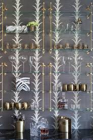 schumacher acanthus wallpaper dresses up a contemporary wall of a bar design finished with stacked glass and brass french shelves