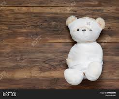 portrait of cute mummy teddy bear doll bind with white gauze or bandage on dark wooden background used as background wallpaper or backdrop in