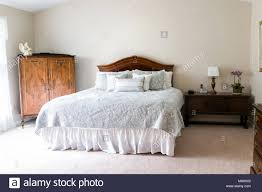 bedroom staging. Closeup Of New Bed With Headboard, Decorative Pillows, Comforter, In Bedroom Staging Model Home, House Or Apartment By Window Sunlight
