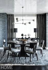 a moroccan silk rug and black and silver wallpaper strike a sumptuous tone in the dining room where a david weeks chandelier illuminates a round