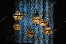 yellow chandeliers hanging next to blue curtain in a dark hall photo by m a n