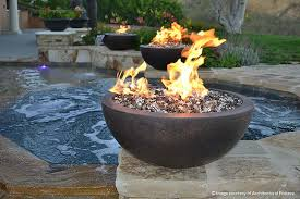 a combination of bronze and ice blue fire glass burns in an outdoor fire bowl