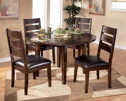 round dark brown wooden table with four legs bined with dark brown wooden chairs having black attracting small round dining
