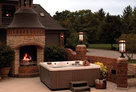 this unique hot tub landscape includes a backyard spa framed by a brick wall landscape and an outdoor fireplace