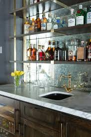 a rustic wet bar boasts dark stained oak cabinets ed with a glass door beverage fridge