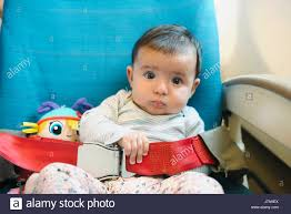baby girl sitting on a plane seat with a doll and the seat belt fastened
