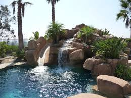 Rock Swimming Pool with Slide, Waterfall and a Table in the pool. tropical