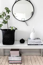 simple and minimal scandinavian style entryway with a round mirror