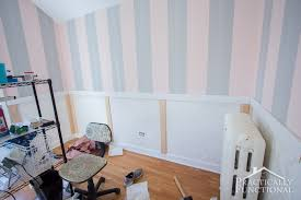 diy wainscoting with textured wallpaper inside the panels prior to painting