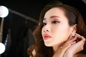 pretty young woman with makeup putting on an earring in front of mirror