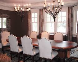 seven white upholstered dining chairs with big wooden table and double rustic chandelier