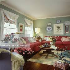 living room cottage style eclectic mixed styles rasberry colored sofas sage green walls with white trim