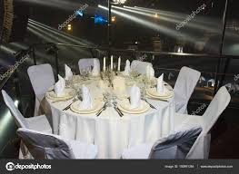 wedding banquet the chairs and round table for guests served with cutlery and