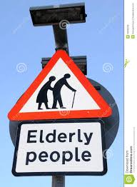 elderly people crossing sign in a red triangle against a blue sky