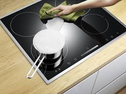 hands cleaning an electric stovetop
