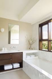Set within a Calacatta Caldia marble surround, a Kohler tub offers a  bathroom a view