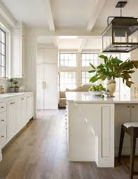 A Seeded Glass Carriage Lantern Illuminates An Off White Kitchen Island  Topped With White Quartz And Accented With Ornate Wood Trim Moldings Lined  With ...