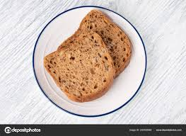 Slices Of Grain Bread With Mold On A White Plate With A Blue Stripe