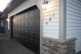elegant house with black garage doors