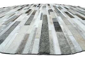 gray cowhide rug view of a round gray cowhide patchwork rug designed in stripes gray brown gray cowhide rug