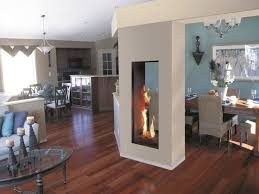 high vertical gray double sided gas fireplace is dividing decorative brown dining table set also neutral living room seating area with oval glass table