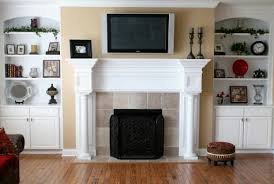 custom home family room flat screen tv mounted over fireplace hand carved mantle built in bookcase