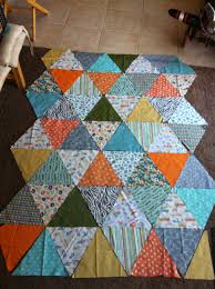 DIY-Triangle Quilt | Project: Leasa & Start with cutting 2 triangles of each print. Start arranging however you  like, then decide how many more to cut of which fabrics to fill your holes. Adamdwight.com