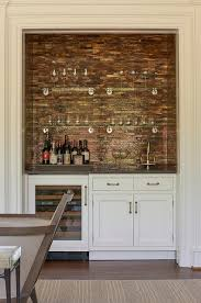 living room bar nook is filled with white cabinets fitted with a wine cooler topped with gray quartz framing a sink under a shimmery copper mosaic tiled