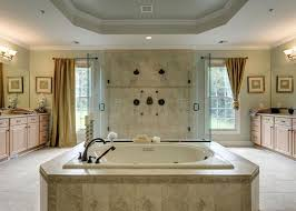 luxury bathroom with travertine tile with dual showerheads and central enclosed tub