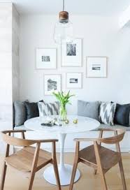 a wood and gl light pendant hangs over a saarinen dining table seating two mid century modern dining chairs and a white built in dining bench topped with