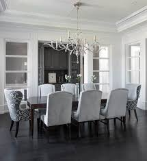 gray dining room features a tray ceiling accented with a satin nickel and glass chandelier illuminating a dark stained curved dining table lined wi