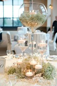 picture of an oversized glass with baby s breath and a candle holder baby s breatj and pearls to cover the table and candles