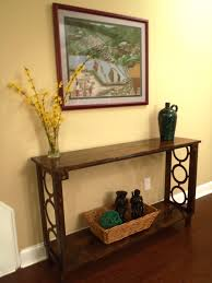 metal hall table. Antique Brown Wooden Narrow Console Table With Round Metal Accent And Small Rattan Basket On Floor Hall