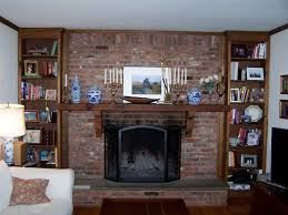 painted brick fireplace with red brick stone fireplace having brown wooden storage and