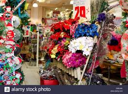 Stock Photo - Store having sale on Christmas decorations, including blue,  purple, and red faux poinsettias, Oaxaca. Mexico